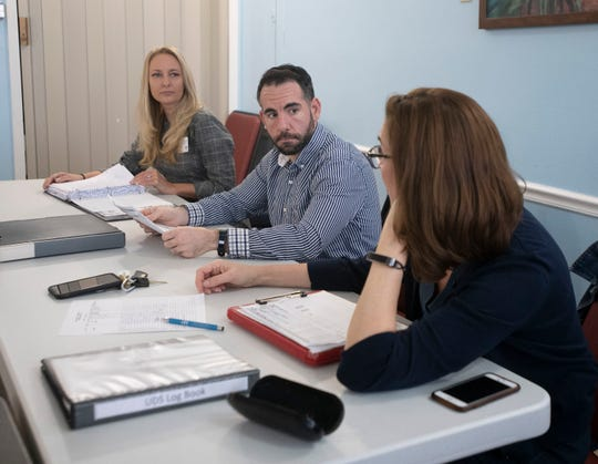 Mental health professionals Amy Gokey, Johnathan Hoffman and Meg Doherty review patient care Friday during a meeting at The Friary in Gulf Breeze on Friday.