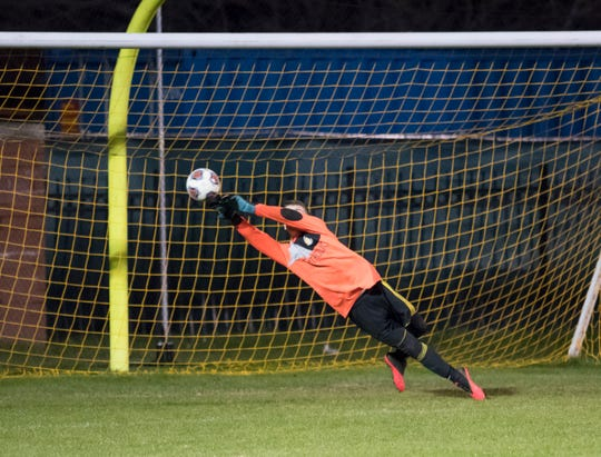 Crusaders goalie William Stanley (1) dives to make a save during the Tate vs Catholic boys soccer game at Pensacola Catholic High School in Pensacola on Wednesday, Jan. 29, 2020.