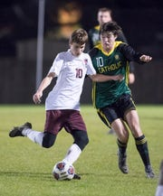 Nathan Bailey (10) gets set to pass the ball under pressure of John Birdwell (10) during the Tate vs Catholic boys soccer game at Pensacola Catholic High School in Pensacola on Wednesday, Jan. 29, 2020.