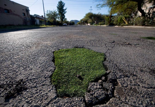"""Janet Miller, a resident in the Armory Park Neighborhood, and friend Elizabeth Garber filled in several potholes with fake grass at Fourth Avenue and 16th Street in Tucson not out of anger and frustration, but """"just for the fun of it."""""""