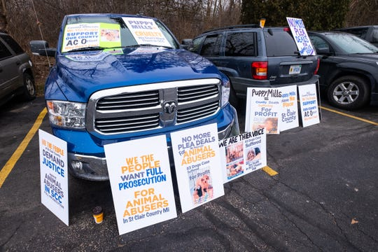 Signs are arranged around vehicles parked outside the 72nd District Court after a protest for the sentencing of Irene Burns Friday, Jan. 31, 2020, in Marine City. Burns pleaded guilty to a misdemeanor of attempted animal abandonment or cruelty for four to 10 animals at a hearing in December, and was sentenced to 30 days in jail and two years' probation.