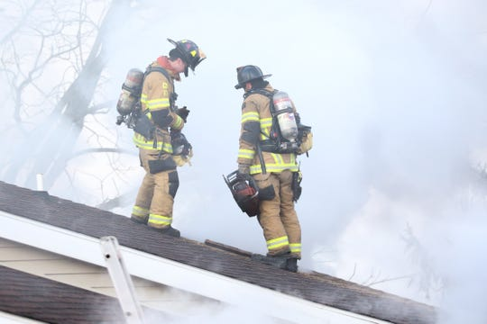 Fire fighters work on the roof of a house in the 8900 block of Mentzer Gap Road, Quincy Township, on Friday morning, Jan. 31, 2020.