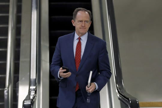 Sen. Pat Toomey, R-Pa., takes an escalator down in the basement of the U.S. Capitol in Washington, Thursday, Jan. 30, 2020, during the impeachment trial of President Donald Trump on charges of abuse of power and obstruction of Congress. (AP Photo/Julio Cortez)