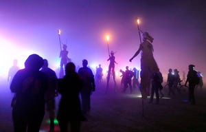 Burners on stilts walk with the procession leading up to burning of the man during Burning Man 2014
