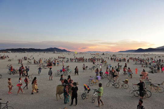 Burners mingle about near an art installation on the playa on Tuesday evening August 27, 2019.