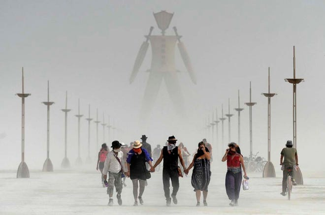 Burners walk from the man during a dust storm at Burning Man 2014