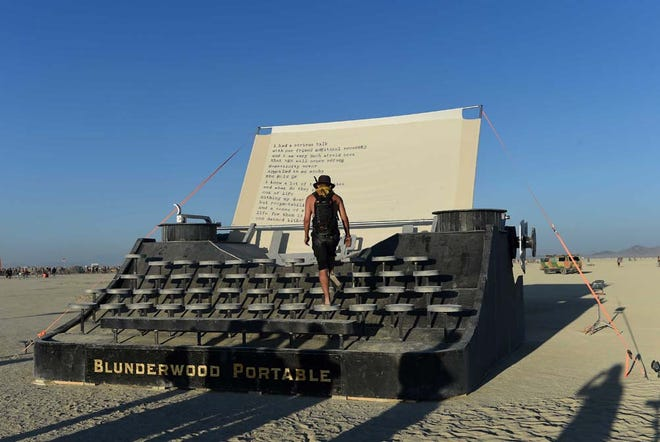 A burner walks on the Blunderwood Portable giant typewriter by artist Jason Turgeon and his crew at Burning Man 2015