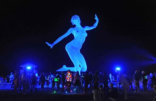 People gather around the art sculpture Bliss Dance by Marco Cochrane at Burning Man on Wednesday night Sept. 1, 2010.