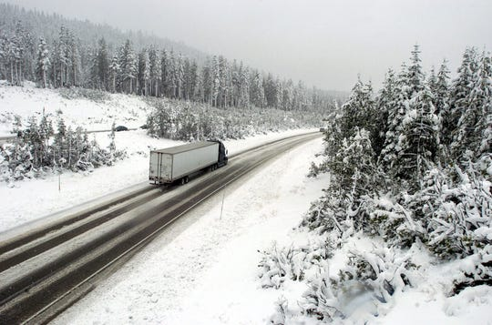 A truck slowly makes its way over the Sierra Nevada on Interstate 80 at Soda Spring during a snowstorm, Tuesday, Oct. 19, 2004. Photo by David B. Parker.