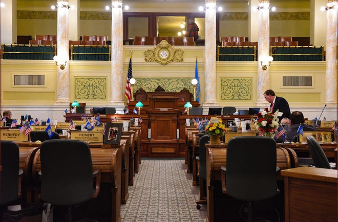 A few senators prepare things at their desk before the legislative session begins on Tuesday, Jan. 14, at the State Capitol in Pierre.