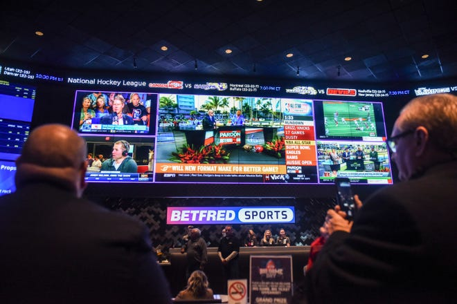 People watch as a ribbon is cut during the opening of Betfred sportsbook on Thursday, Jan. 30, 2020 at Grand Falls Casino in Larchwood, Iowa.