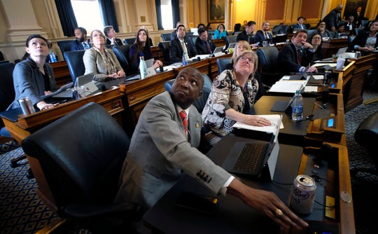 Del. Don Scott, Jr., D-Portsmouth, foreground, and other Democratic colleagues look up at the voting board as they vote to pass one of a number of gun-related bills during the floor session of the Virginia House of Delegates inside the State Capitol in Richmond Jan. 30.