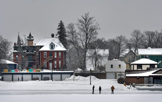 Gloomy gray skies loom over the neighborhood as people walk on an ice-covered Lake George in the afternoon Friday, Jan. 31, 2020, in St. Cloud.