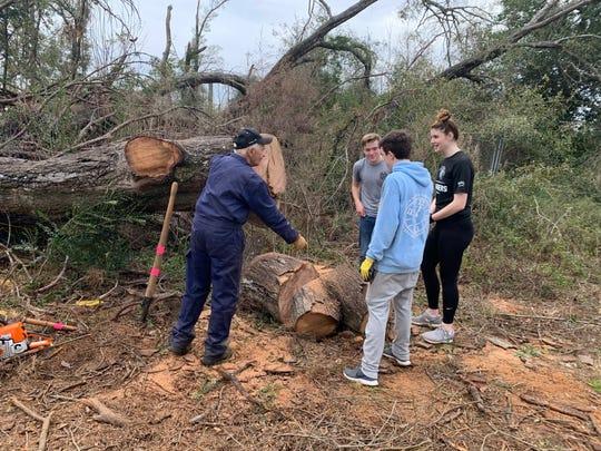 Gary Fitzgerald, 77, left, helps clear Hurricane Michael debris in Marianna.