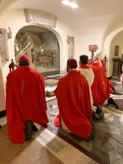 Bishop Mark J. Seitz and Vicar General Benjamin Flores-Ruiz pray Jan. 20, 2020, at the tomb of St. Peter, along with other bishops from Region X.