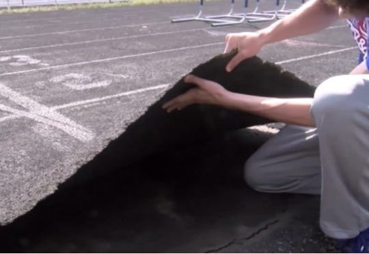 A student lifts the damaged track at Nekoosa High School.