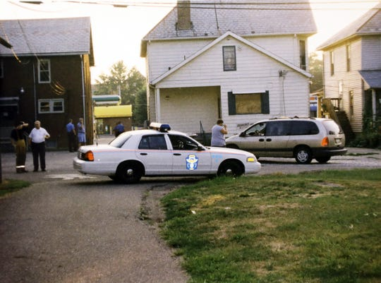A crime scene photograph from the scene where Michael Martin III shot 9-year-old Michael Derwacter in 2002. Martin shot Derwacter, who was riding his bike in an alley behind Martin's house, from the window above the hood of the police cruiser.