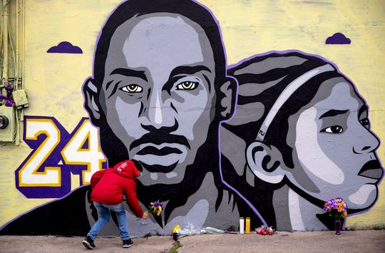 Enzo Maugars places a bouquet of purple and gold flowers at the base of a new tribute mural honoring Kobe Bryant and his daughter, Gianna in Austin, Texas. The mural, located behind the Sushi Hi restaurant along Guadalupe Street, was created by Texas-based artist Laced and Found with help from Snuk One and Riki Loring.
