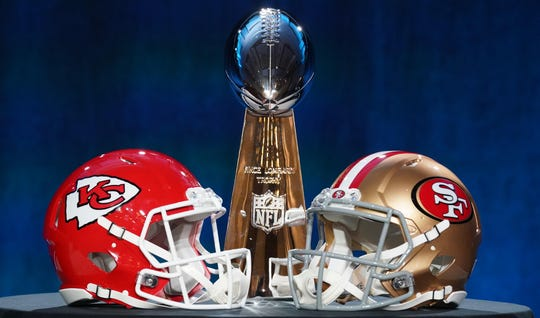 Helmets for the Chiefs and 49ers are placed in front of the Vince Lombardi Trophy.