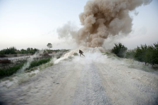 US Marine Sergeant Anthony Zabala runs to safety as an IED explodes in Helmand Province, Afghanistan, on July 13, 2009.