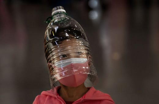 A Chinese girl wears a plastic bottle as makeshift homemade protection and a protective mask while waiting to check in to a flight at Beijing Capital Airport on Jan. 30, 2020 in Beijing, China. The number of cases of a deadly new coronavirus rose to over 7000 in mainland China Thursday as the country continued to lock down the city of Wuhan in an effort to contain the spread of the pneumonia-like disease which medicals experts have confirmed can be passed from human to human. In an unprecedented move, Chinese authorities put travel restrictions on the city which is the epicenter of the virus and neighboring municipalities affecting tens of millions of people. The number of those who have died from the virus in China climbed to over 170 on Thursday, mostly in Hubei province, and cases have been reported in other countries including the United States, Canada, Australia, Japan, South Korea, and France. The World Health Organization  has warned all governments to be on alert, and its emergency committee is to meet later on Thursday to decide whether to declare a global health emergency.