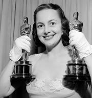 "Olivia de Havilland holds up her two trophies after winning a second best actress Oscar in 1950 for her performance in ""The Heiress."" Her first win came in 1947 for ""To Each His Own."""