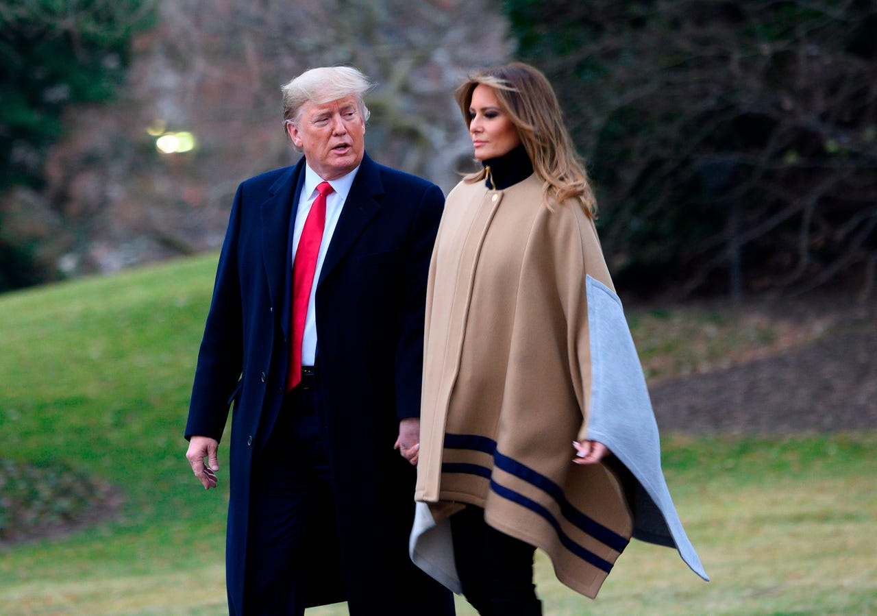President Donald Trump and first lady Melania Trump depart White House for a weekend at their Mar-a-Lago resort in Florida, Jan. 31, 2020. She wore a tan poncho with dark trim and pale blue patches, with tall suede boots.