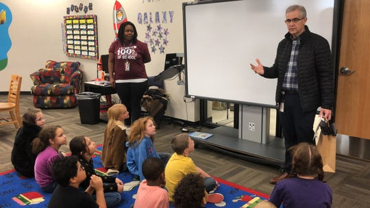 Abilene ISD Superintendent David Young, right, explains to a Bowie Elementary class why library assistant Amber West is the latest Impact Award winner. The district created the awards earlier this school year to recognize employees who make the school experience meaningful and positive.