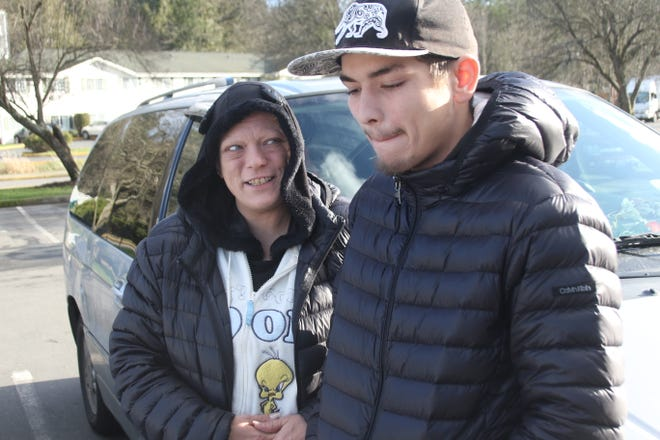 Zachary, right, and his mother, Thea, left, stand outside the minivan they have lived out of for more than two years. With Zachary recovering from heart surgery in January, community donations provided the family with a temporary stay in a Port Orchard hotel.
