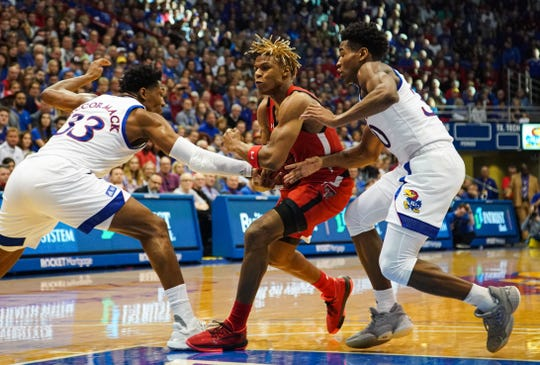 Feb 1, 2020; Lawrence, Kansas, USA; Texas Tech Red Raiders guard Jahmi'us Ramsey (3) drives against Kansas Jayhawks forward David McCormack (33) and guard Ochai Agbaji (30) during the first half at Allen Fieldhouse. Mandatory Credit: Jay Biggerstaff-USA TODAY Sports