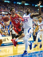 Feb 1, 2020; Lawrence, Kansas, USA; Texas Tech Red Raiders guard Davide Moretti (25) passes the ball as Kansas Jayhawks center Udoka Azubuike (35) defends during the first half at Allen Fieldhouse. Mandatory Credit: Jay Biggerstaff-USA TODAY Sports