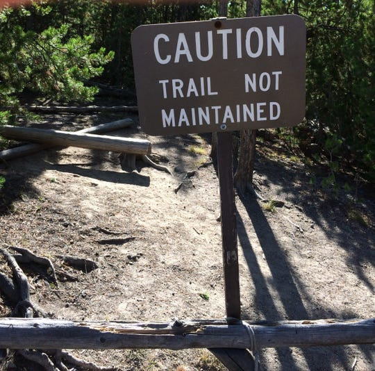"""Some trails at Yellowstone National Park were closed because of poor conditions, while others were marked with """"Caution, Trail not Maintained"""" signs like the one show here."""