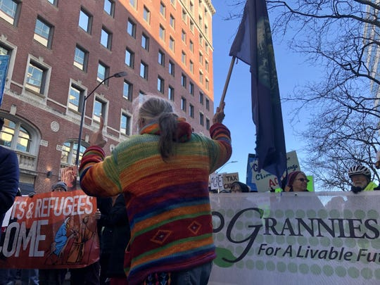 """Blair Frank led a  group chant, """"One global family,"""" as climate change activists filled up Locust Street between 5th and 4th avenues Saturday around noon."""