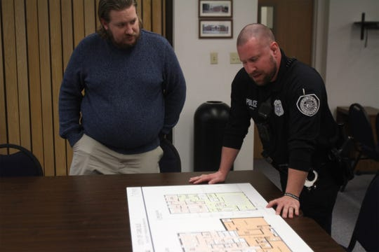 Carlisle city administrator Deven Markley watches as Carlisle Police chief Matt Koch describes some of the features of the new police department design.