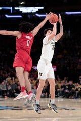 Michigan's Brandon Johns Jr. shoots over Rutgers guard Geo Baker in the first half Saturday, Feb. 1, 2020, in New York.