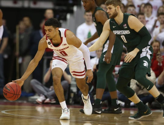 Wisconsin guard D'Mitrik Trice chase a loose ball as Michigan State guard Kyle Ahrens defends during the first half on Saturday, Feb. 1, 2020, in Madison, Wis.