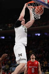 Michigan's Austin Davis dunks in front of Rutgers' Geo Baker during the first half Saturday, Feb. 1, 2020, in New York.