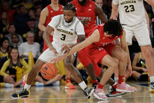 Michigan's Zavier Simpson and Rutgers' Mamadou Doucoure fight for control of the ball during the first half Saturday, Feb. 1, 2020, in New York.