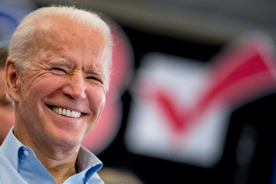 Democratic presidential candidate former Vice President Joe Biden smiles as former Secretary of State John Kerry speaks at a campaign stop at the South Slope Community Center, Saturday, Feb. 1, 2020, in North Liberty, Iowa.