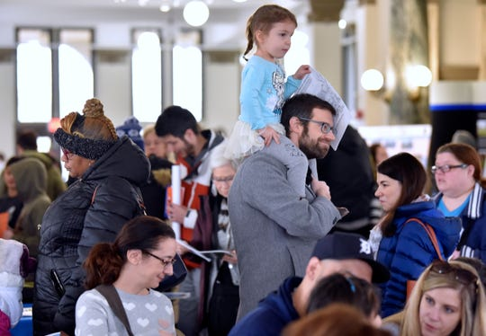 Claire Schultz, 3, rides on the shoulders of her father, John Schultz, as they attend the event with mother and wife, Elizabeth, second from right.