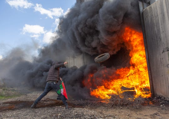 A protester burns tires by an Iron gate in the Israeli separation wall during a protest against Israel and the Untied States in the West Bank village of Bil'in, near Ramallah, Friday, Jan. 31, 2020.