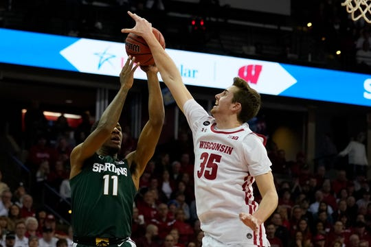 Wisconsin's Nate Reuvers (35) blocks a shot by Michigan State's Aaron Henry (11) during the first half.
