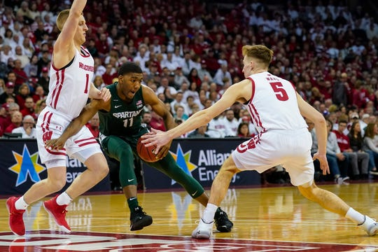 Michigan State's Aaron Henry (11) battles between Wisconsin's Brevin Pritzl (1) and Tyler Wahl (5) during the first half.