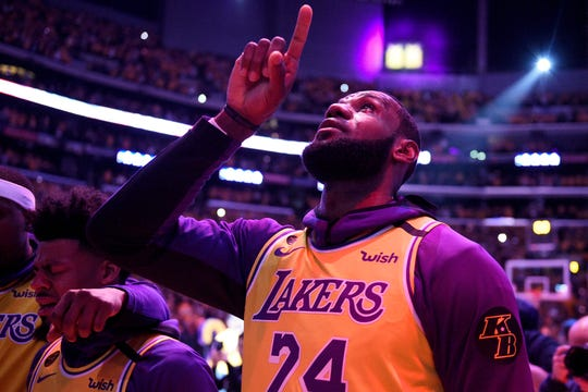 Los Angeles Lakers' LeBron James, wearing a No. 24 jersey, points up while shedding tears after the national anthem before the team's game Friday against the Portland Trail Blazers in Los Angeles.