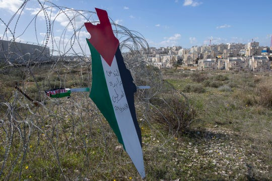 """Protesters post a placard with the colors of the Palestinian flags and Arabic that reads """"Jerusalem is the eternal capital of Palestine,"""" during a protest against Israel and the Untied States in the West Bank village of Bil'in, near Ramallah, Friday, Jan. 31, 2020."""