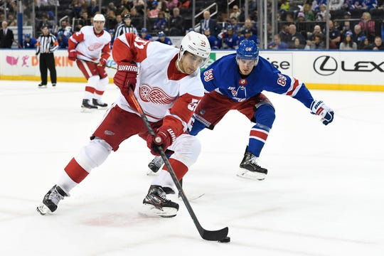 Detroit Red Wings center Valtteri Filppula skates with the puck as New York Rangers right wing Pavel Buchnevich defends during the first period.