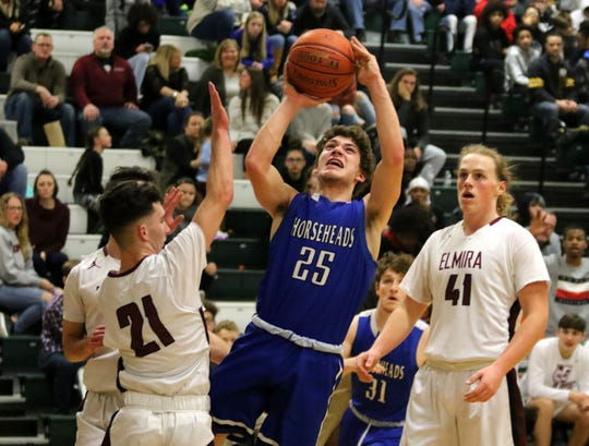 Grayson Woodhouse of Horseheads drives between Elmira's Zack Odum (21) and Trey Hawken (41) during the Express' 47-37 win in  in boys basketball Jan. 31, 2020 at Elmira High School.