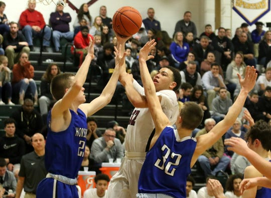 Elmira's Devin Dennard drives the lane in between Horseheads' Andrew McLaughlin (left) and Patrick Smith (32) during the Express' 47-37 win in boys basketball Jan. 31, 2020 at Elmira High School.