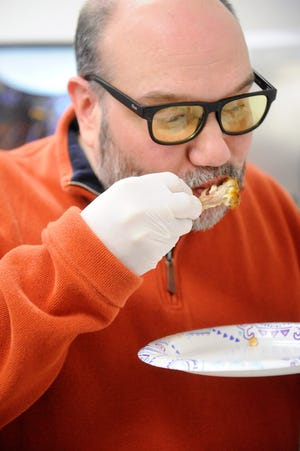 Courier & Press Consumer Experience Director Joshua Jenkins enjoys one of 10 chicken wings tasted in the Courier office on Friday, Jan. 31, 2020.