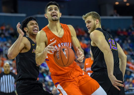 Evansville's Sam Cunliffe (20) drives to the basket after splitting defense from Northern Iowa's Trae Berhow (11) and Justin Dahl (15) as the Evansville Purple Aces play the league leading Northern Iowa Panthers at the Evansville Ford Center Saturday afternoon, February 1, 2020.